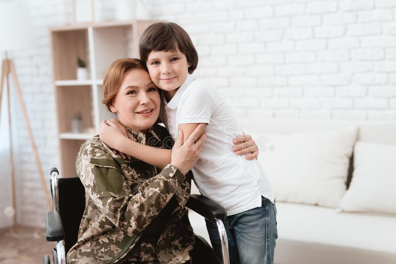 Veterano de la mujer en la silla de ruedas vuelta a casa El hijo abraza a la mamá en silla de ruedas fotos de archivo libres de regalías