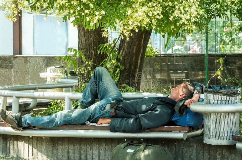 Veterano desabrigado Sono militar ex pobre do soldado do homem desabrigado com fome e cansado na máscara no banco no soci urbano  imagens de stock