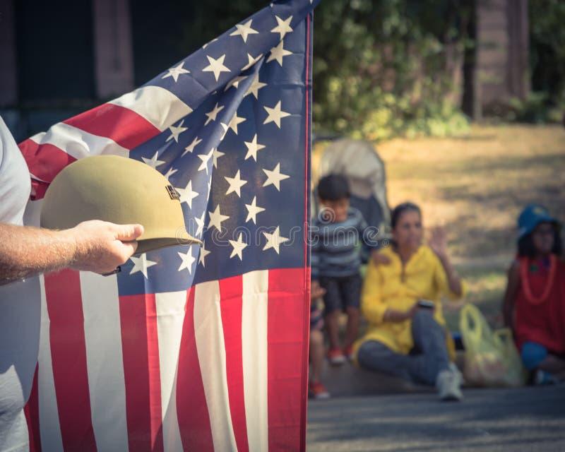 Veterano do tom do vintage com bandeira dos E.U. e capacete de WWI na parada imagens de stock