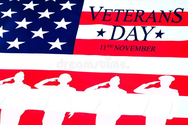 Veterans day background. Text veterans day 11 th november , the USA flag and the shadow of the soldier. Toning royalty free stock photos