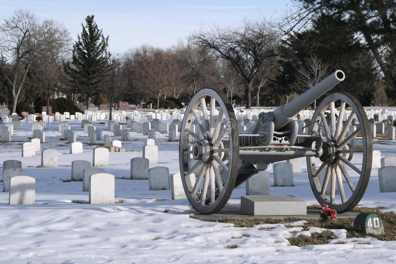 Veterans Day Image. A view of the military section of a historical graveyard depicts the perfect Veterans Day image - a cannon and military grave markers are stock photos