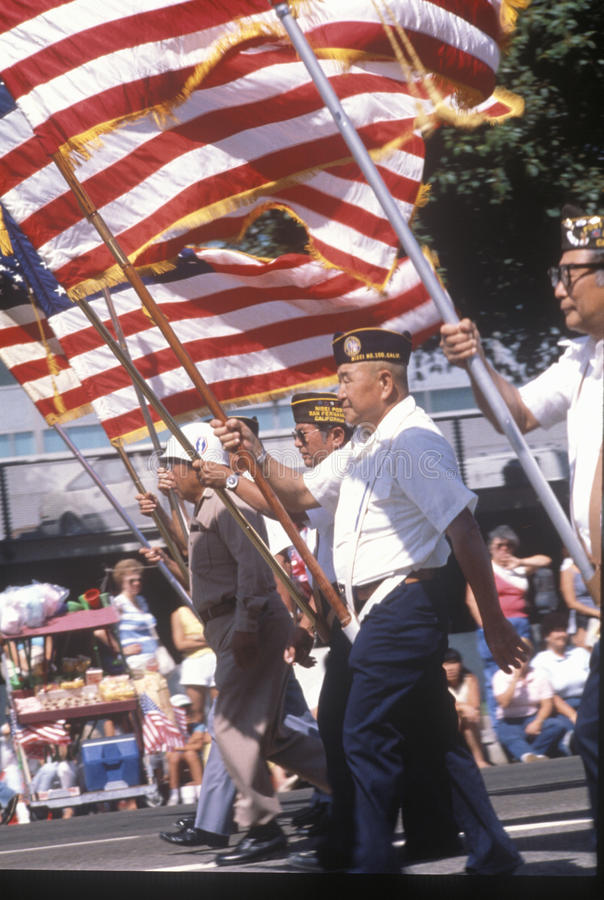 Veterans marching with American Flag stock photos