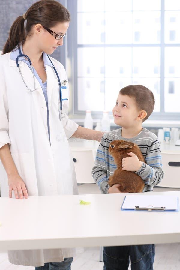 Veterinário e criança de sorriso com coelho do animal de estimação foto de stock