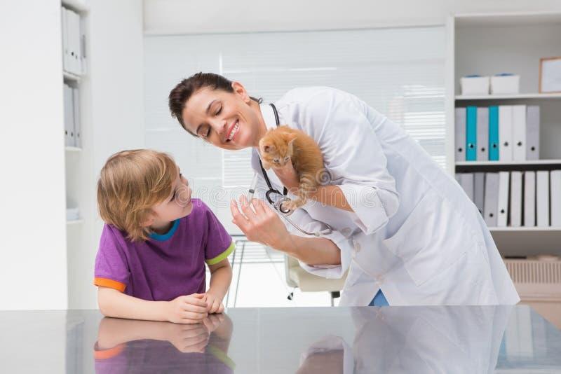 Veterinär- görande injektion på en katt med dess ägare royaltyfri fotografi