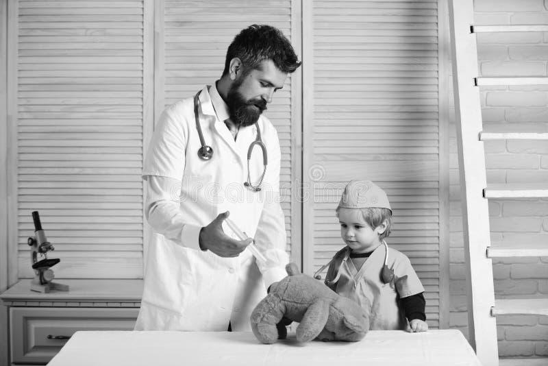 Veterinären och den lilla assistenten gör en injektion till mannen för nallebjörnen med skägget och pojken att rymma injektionssp arkivfoton