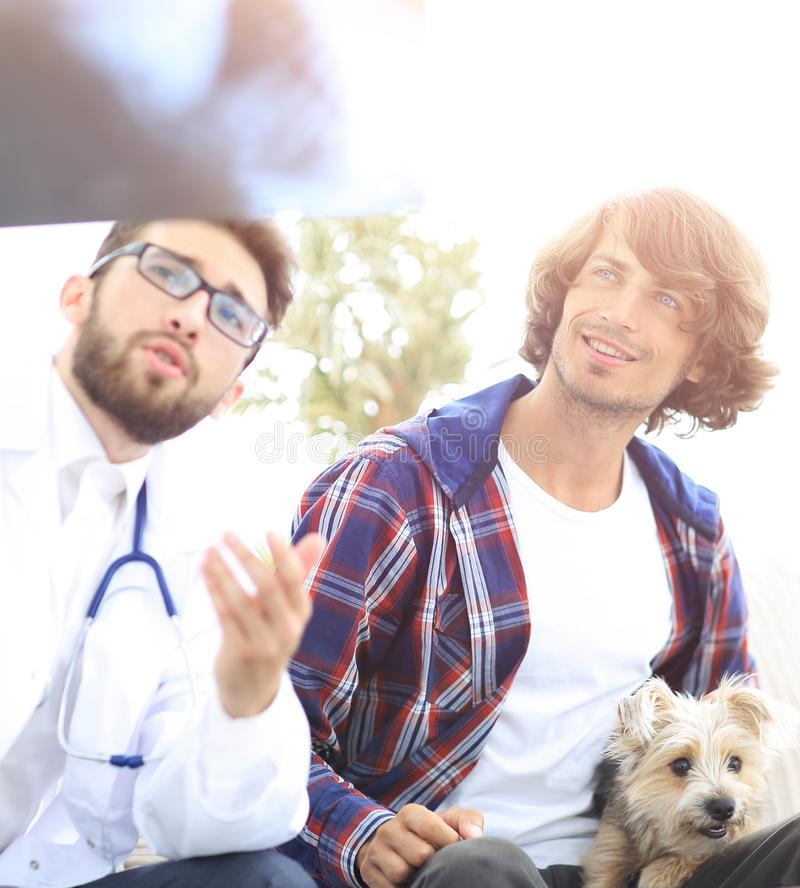Veterinarian showing an x-ray to the owner of the dog. stock photos