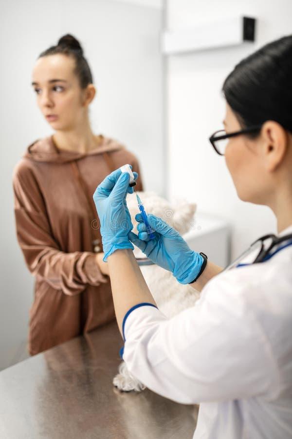 Veterinario en los guantes que sostienen la jeringuilla antes de hacer la inyecci?n para el perro foto de archivo