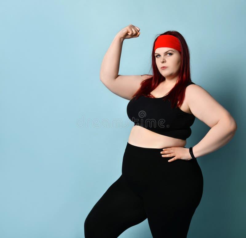 Vetgember-vrouwtje in de rode hoofdband, zwarte bovenlaag en beenkappen, fitness armband Haar spieren tonen, glimlachen Blauwe ac stock fotografie