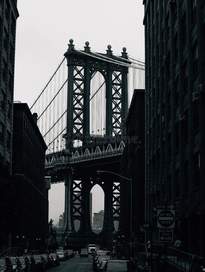Vetical grayscale shot of the Brooklyn Bridge near buildings. A vetical grayscale shot of the Brooklyn Bridge near buildings royalty free stock images