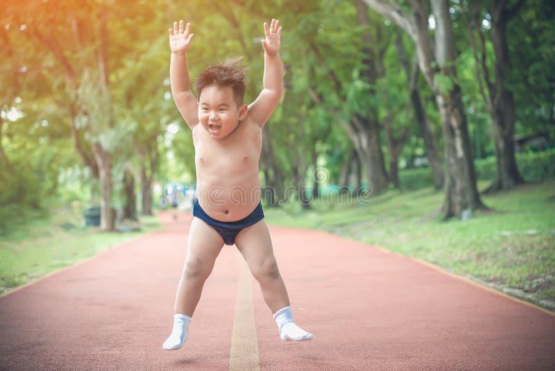 Vetjongen geniet van oefening joggen in het park Kinderen in Chubby hebben gezinsaandacht nodig voor gewichtsverlies voor een gez stock fotografie