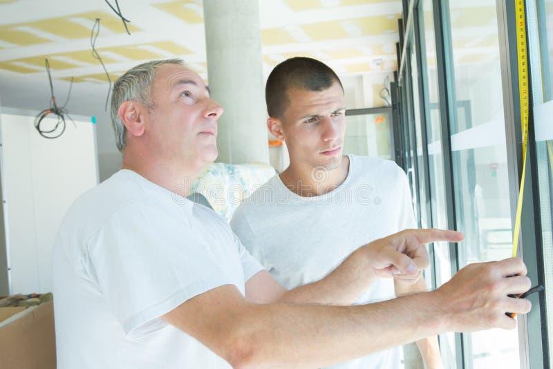 Vetrai che ispezionano la finestra fotografie stock