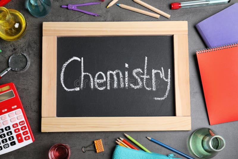 Vetreria per laboratorio, rifornimenti di scuola e bordo con la parola CHIMICA su fondo grigio immagini stock libere da diritti