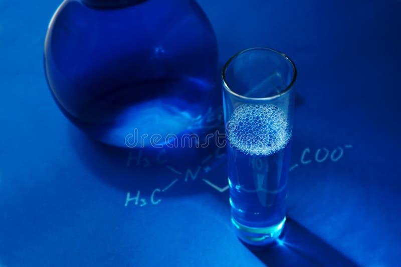 Vetreria per laboratorio su fondo blu fotografia stock