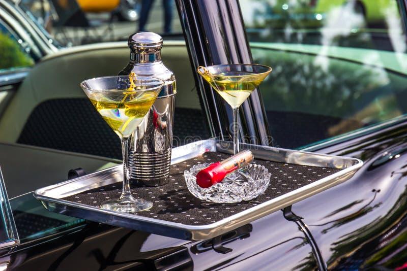 Vetri, agitatore & sigaro di Martini sul vassoio del luppolo dell'automobile immagine stock