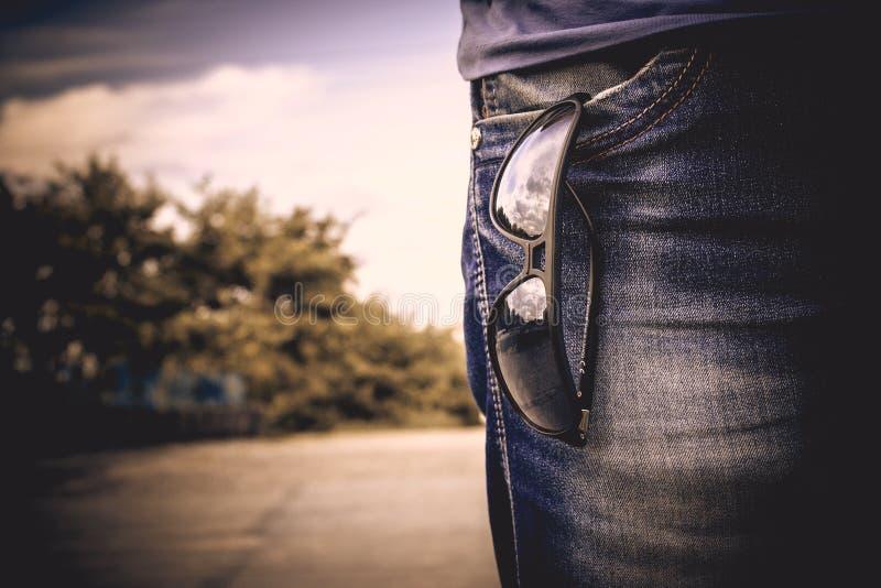 Vetri che appendono sull'i jeans fotografia stock libera da diritti