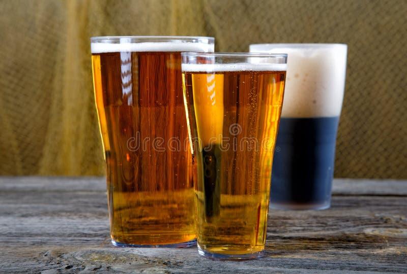 Vetri con birra scura e leggera su una tavola immagine stock