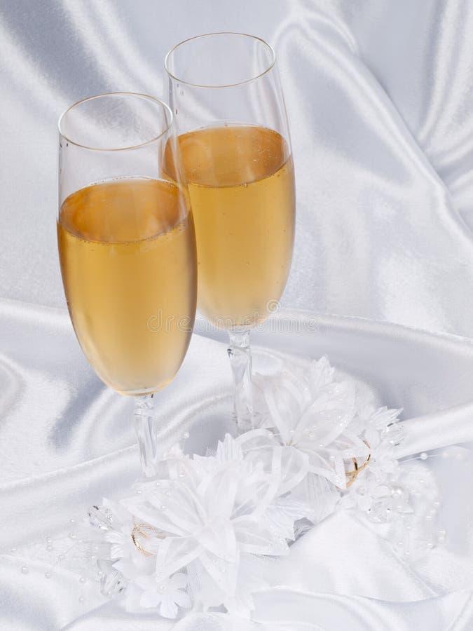 Vetri con champagne e la giarrettiera nuziale immagine stock