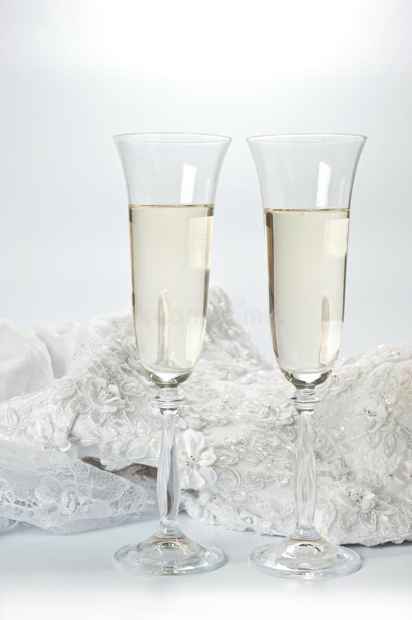 Vetri con champagne ed il vestito da sposa su un fondo bianco immagine stock libera da diritti