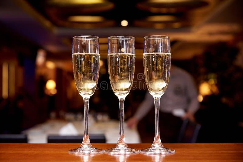 Vetri con champagne sul contatore della barra in un ristorante contro un fondo scuro fotografie stock
