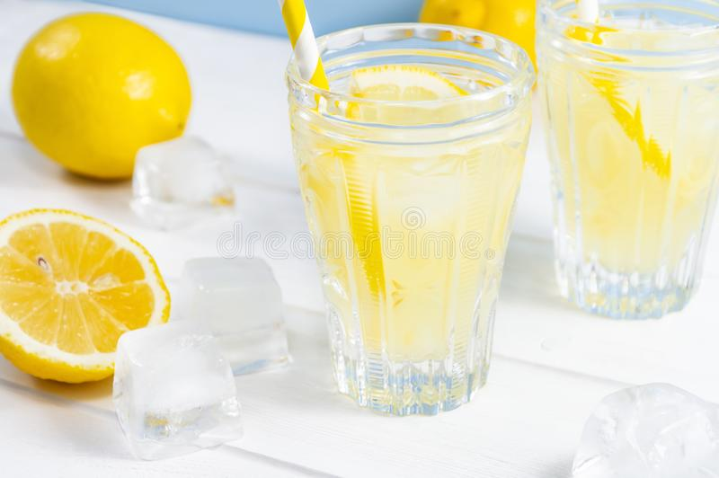 Vetri con la limonata della bevanda di estate, la frutta del limone ed i cubetti di ghiaccio sulla tavola di legno bianca fotografia stock