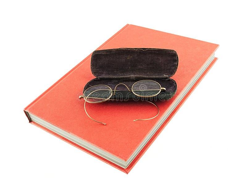 Vetri d'annata che si siedono sopra un libro rosso fotografie stock