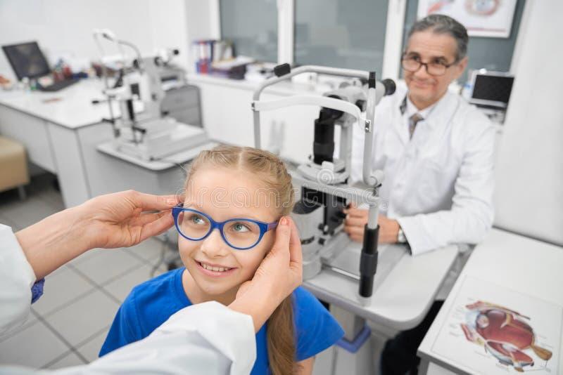 Vetri d'offerta di medico al paziente nella clinica di oftalmologia immagine stock libera da diritti