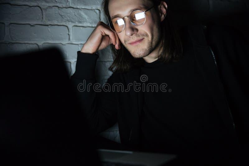 Vetri d'uso concentrati dell'uomo facendo uso del computer portatile immagine stock libera da diritti