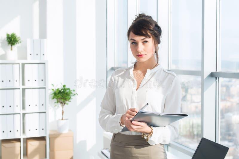 Vetri d'uso del bello, consulente serio e un vestito convenzionale dell'ufficio, giudicando il suo lavoro stazionario, esaminando fotografie stock