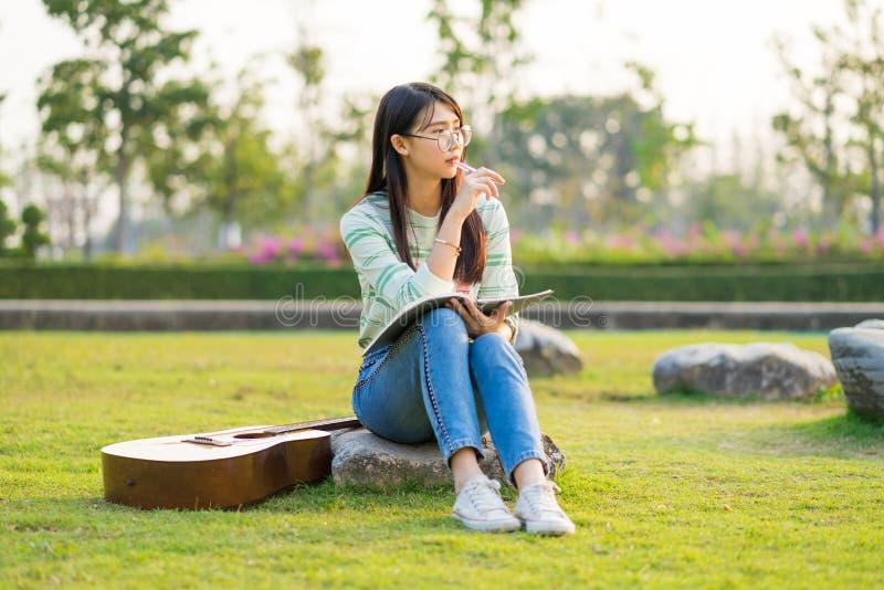 Vetri d'uso dell'adolescente che si siedono sulla roccia con la chitarra ed i libri sul campo di football americano al tramonto fotografia stock