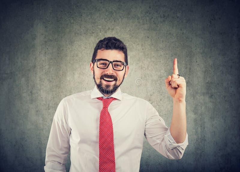 Vetri d'uso dell'uomo d'affari con una buona idea che indica con il suo dito su e sorridere immagine stock libera da diritti