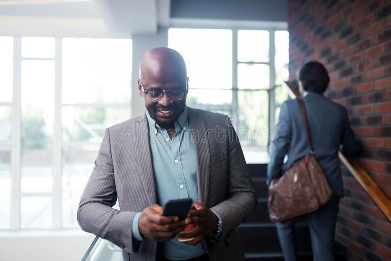 Vetri d'uso dell'uomo d'affari dalla carnagione scura che sorridono mentre leggendo messaggio immagine stock