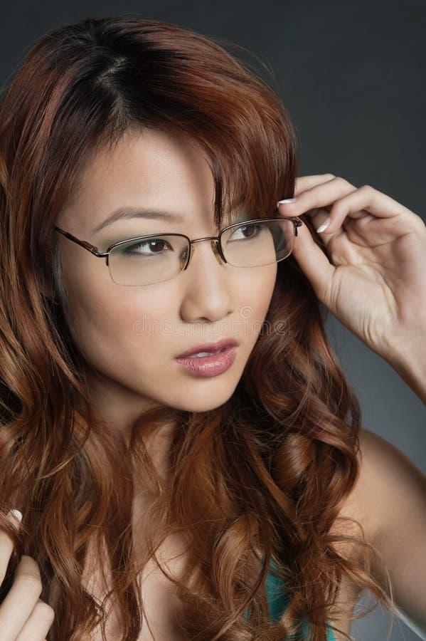 Vetri d'uso della bella donna cinese sopra fondo colorato immagini stock