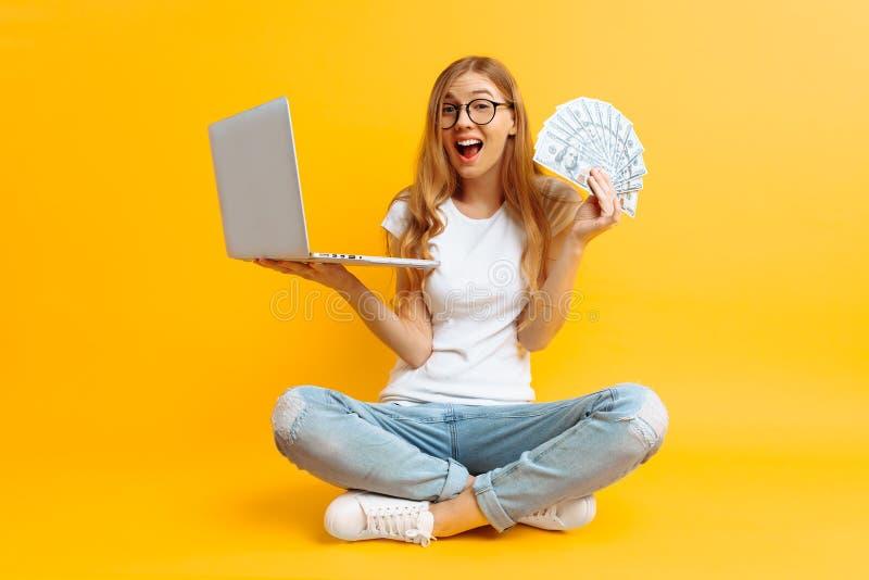 Vetri d'uso della donna che si siedono sul pavimento facendo uso di un computer portatile portatile e che tengono soldi in sua ma immagine stock