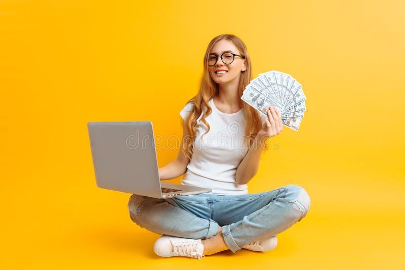Vetri d'uso della donna che si siedono sul pavimento facendo uso di un computer portatile portatile e che tengono soldi in sua ma immagine stock libera da diritti