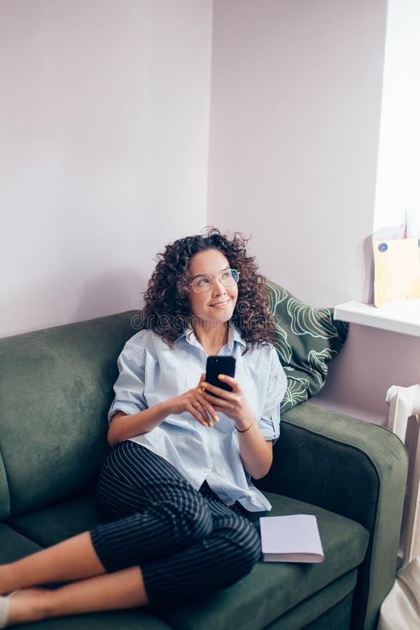 Vetri d'uso della donna graziosa che si trovano sul sofà con il telefono cellulare nella stanza leggera immagini stock