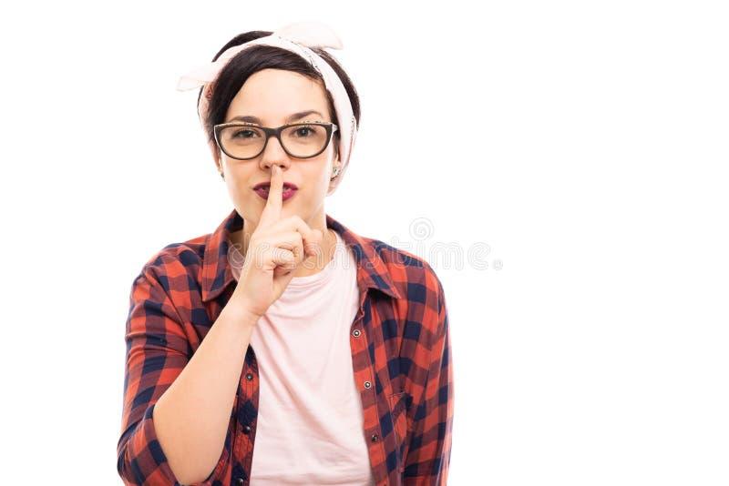 Vetri d'uso della giovane pin-up graziosa che mostrano gesto silenzioso fotografie stock libere da diritti