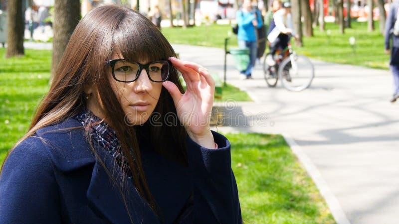 Vetri d'uso della ragazza e raduno aspettante in parco Donna attraente che si siede sul banco che gode della vita all'aperto in p fotografia stock libera da diritti