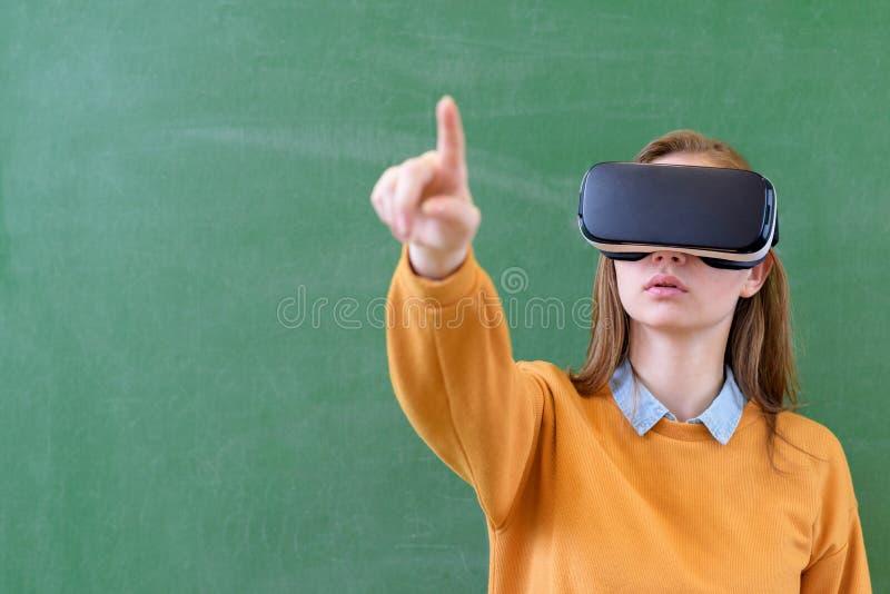 Vetri d'uso di realtà virtuale della studentessa dell'adolescente in aula alla scuola Metodi di insegnamento innovatori immagini stock libere da diritti