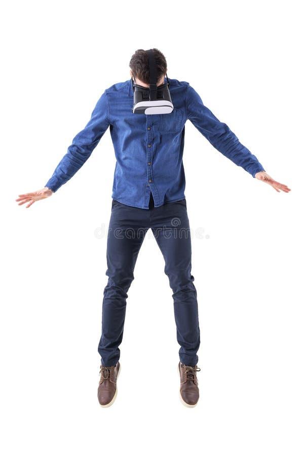 Vetri d'uso sorpresi del vr dell'uomo che saltano e che guardano giù avere esperienza di realtà virtuale immagini stock libere da diritti