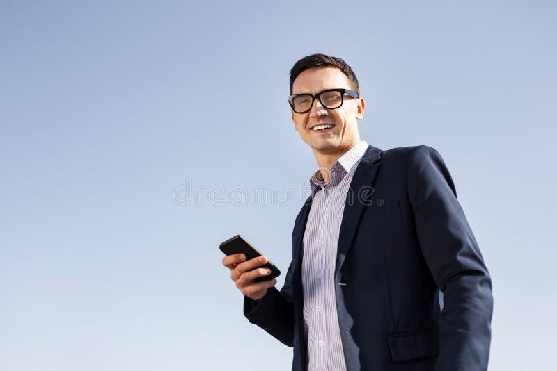 Vetri d'uso sorridenti dell'uomo d'affari bello fotografia stock