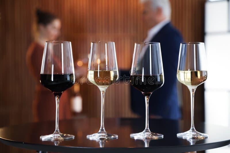 Vetri dei vini differenti contro fondo vago fotografie stock