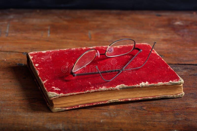 Vetri dell'occhio e del vecchio libro sullo scrittorio di legno immagine stock