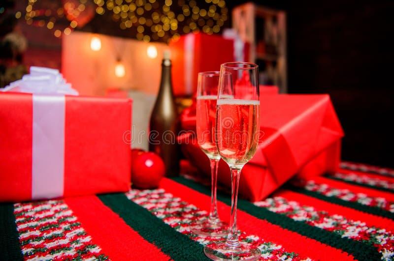 Vetri delle coppie di Champagne Il vetro ha riempito il vino spumante o il champagne vicino ai contenitori di regalo Incoraggia i fotografie stock