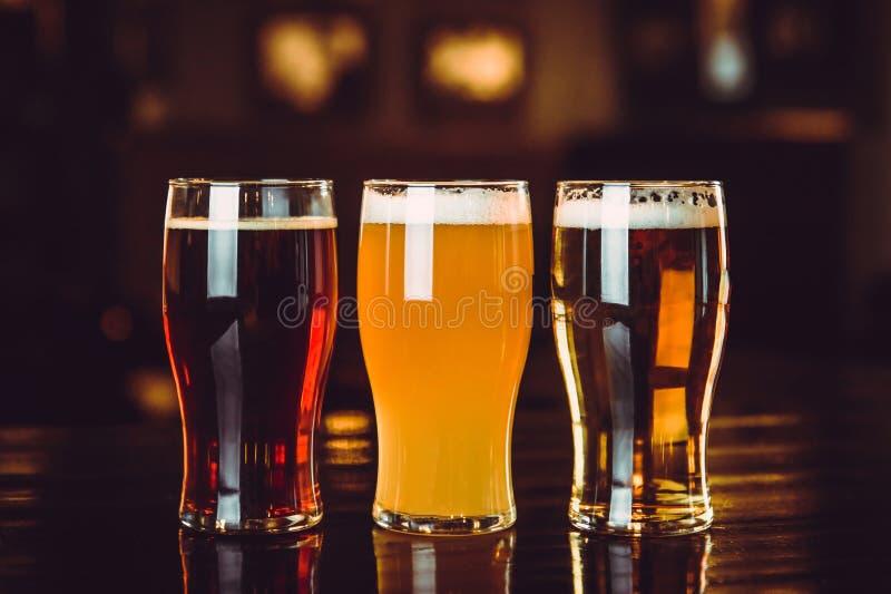 Vetri di birra leggera e scura su un fondo del pub fotografia stock