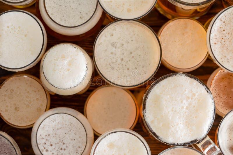 Vetri di birra pieni e schiumosi multipli e dimensioni immagini stock libere da diritti