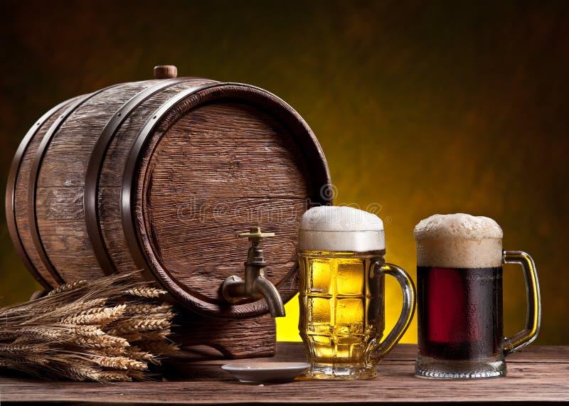 Vetri di birra, vecchio barilotto della quercia ed orecchie del grano. fotografia stock