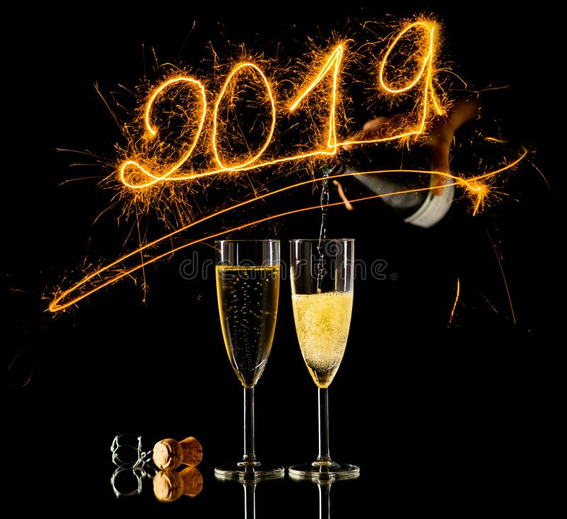 Vetri di champagne e dei numeri dorati del nuovo anno 2019 scritti con i fuochi d'artificio della scintilla sul nero immagini stock libere da diritti