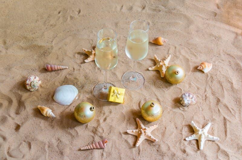 Vetri di Champagne, palle di chrismas e regalo sulla spiaggia immagini stock libere da diritti