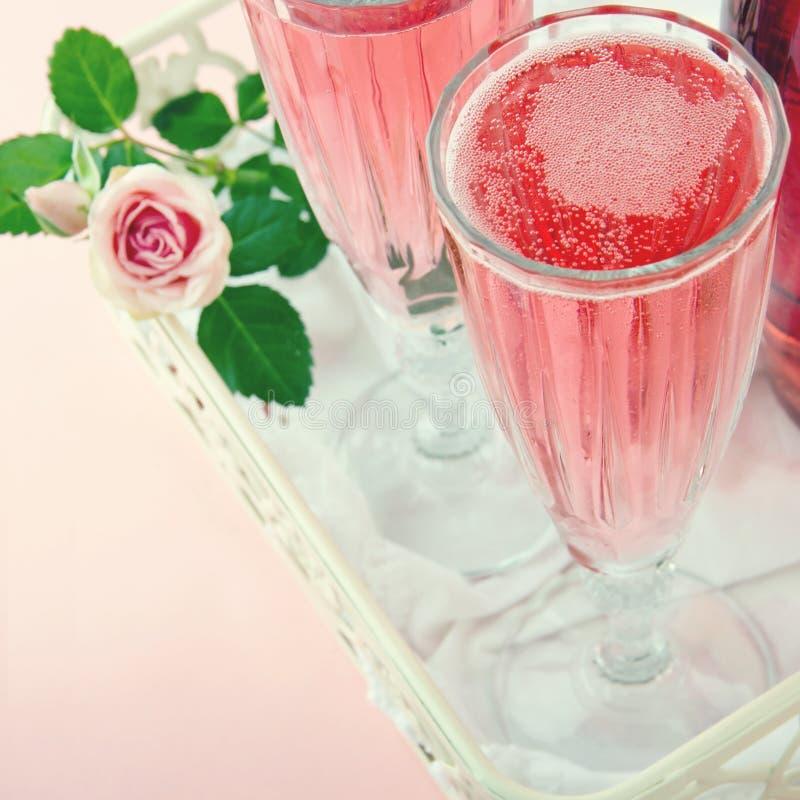 Vetri di champagne rosa con una rosa immagine stock