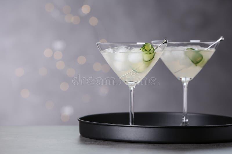 Vetri di martini con il cetriolo sul vassoio contro le luci vaghe fotografie stock